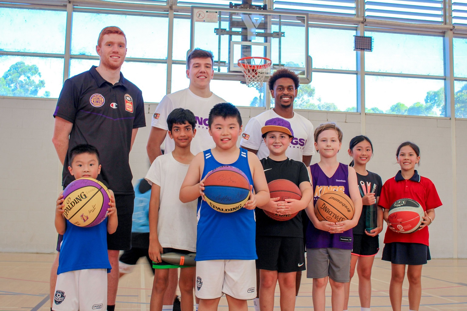 Sydney Kings players Angus Glover, Casper Ware and Dejan Vasiljevic with junior players from the Y NSW Learn to Play Basketball session at Ryde